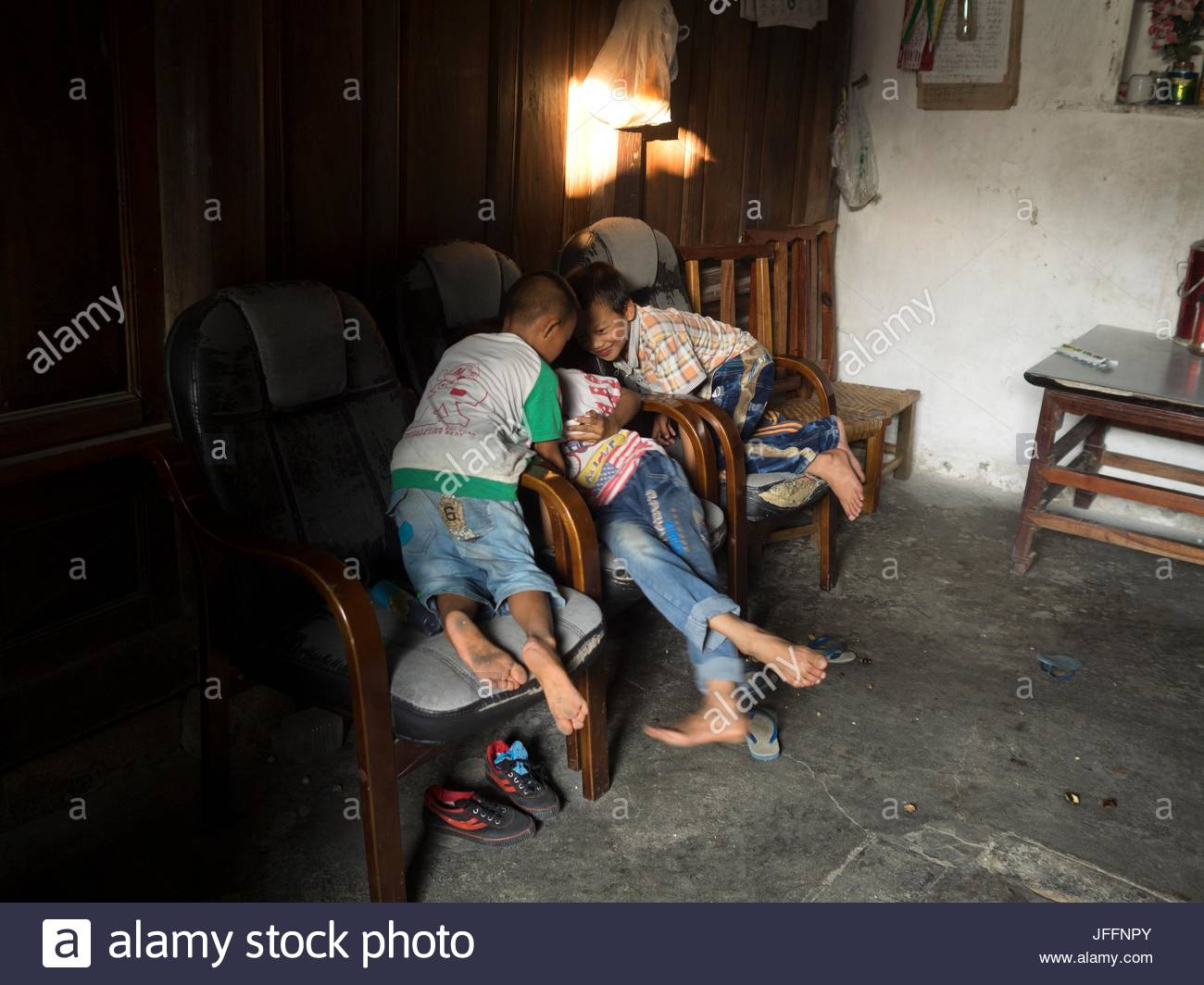 Dai children playing with a cell phone. - Stock Image