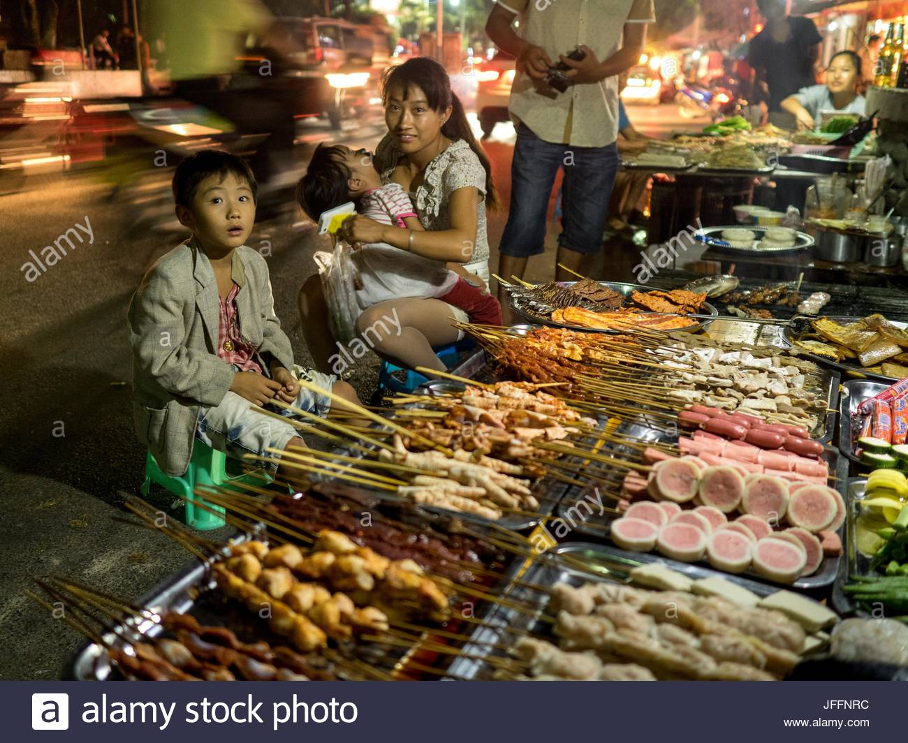 A group of people at a restaurant buffet displaying Chinese food. - Stock Image