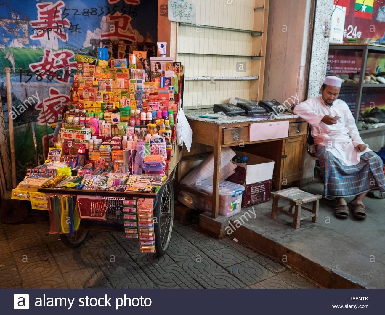 A street vendor checks his cell phone. - Stock Image