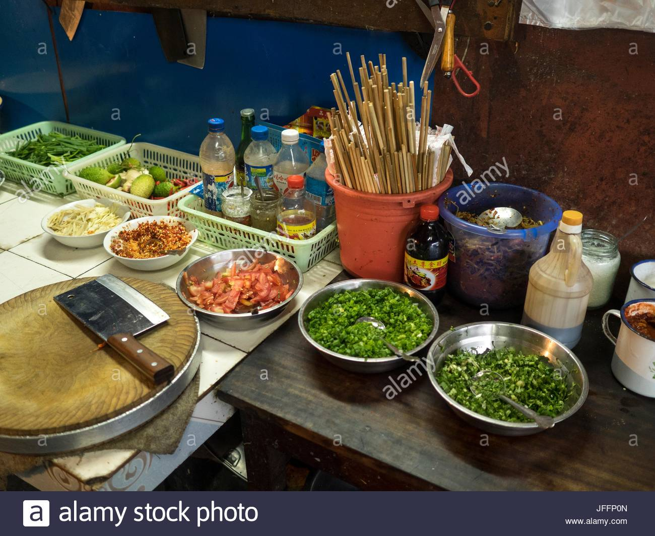Vegetables, a cleaver and sauces in a kitchen at a restaurant in Sudian. - Stock Image