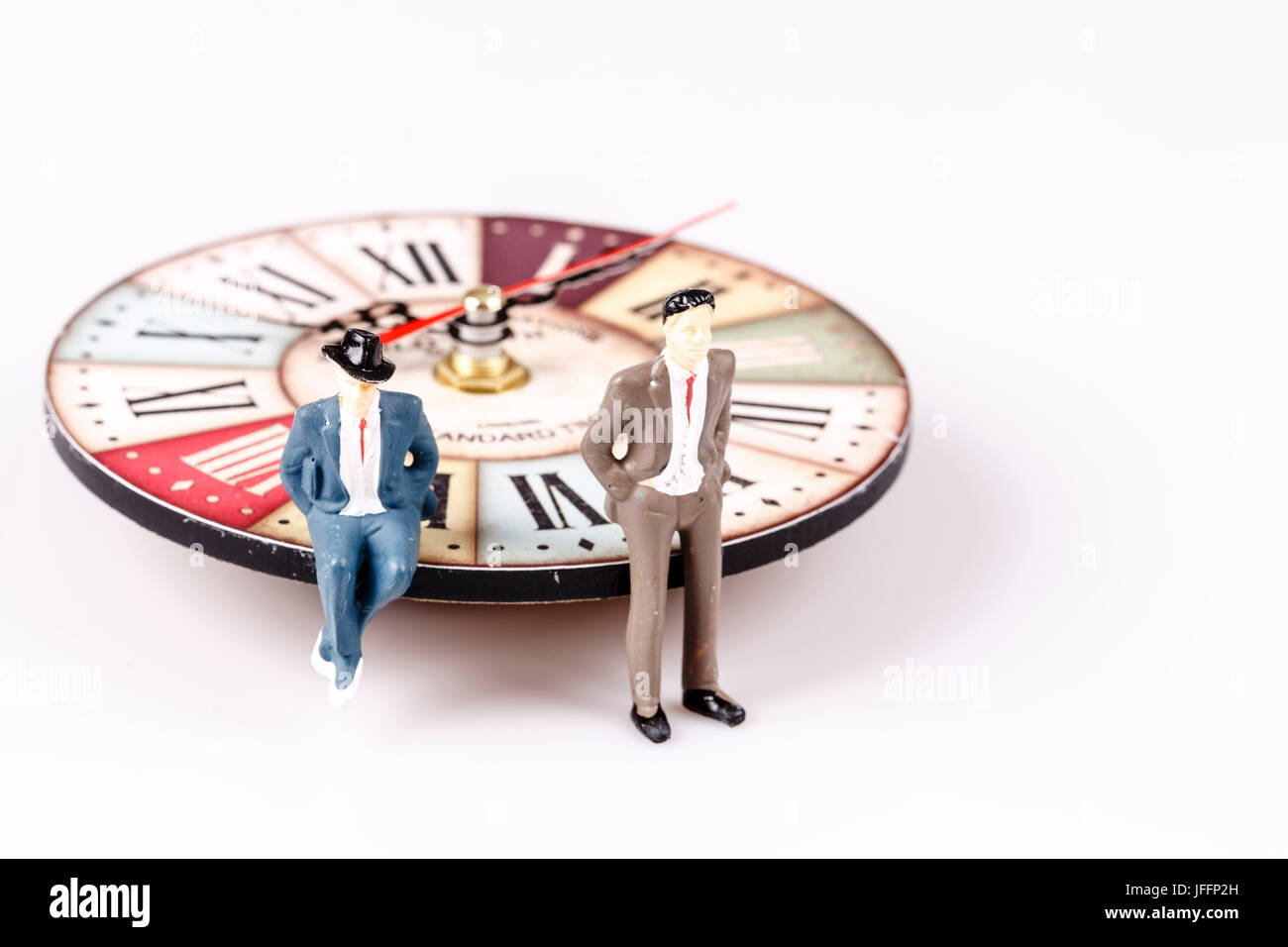 model of man sitting on beautiful old clock on white Stock Photo