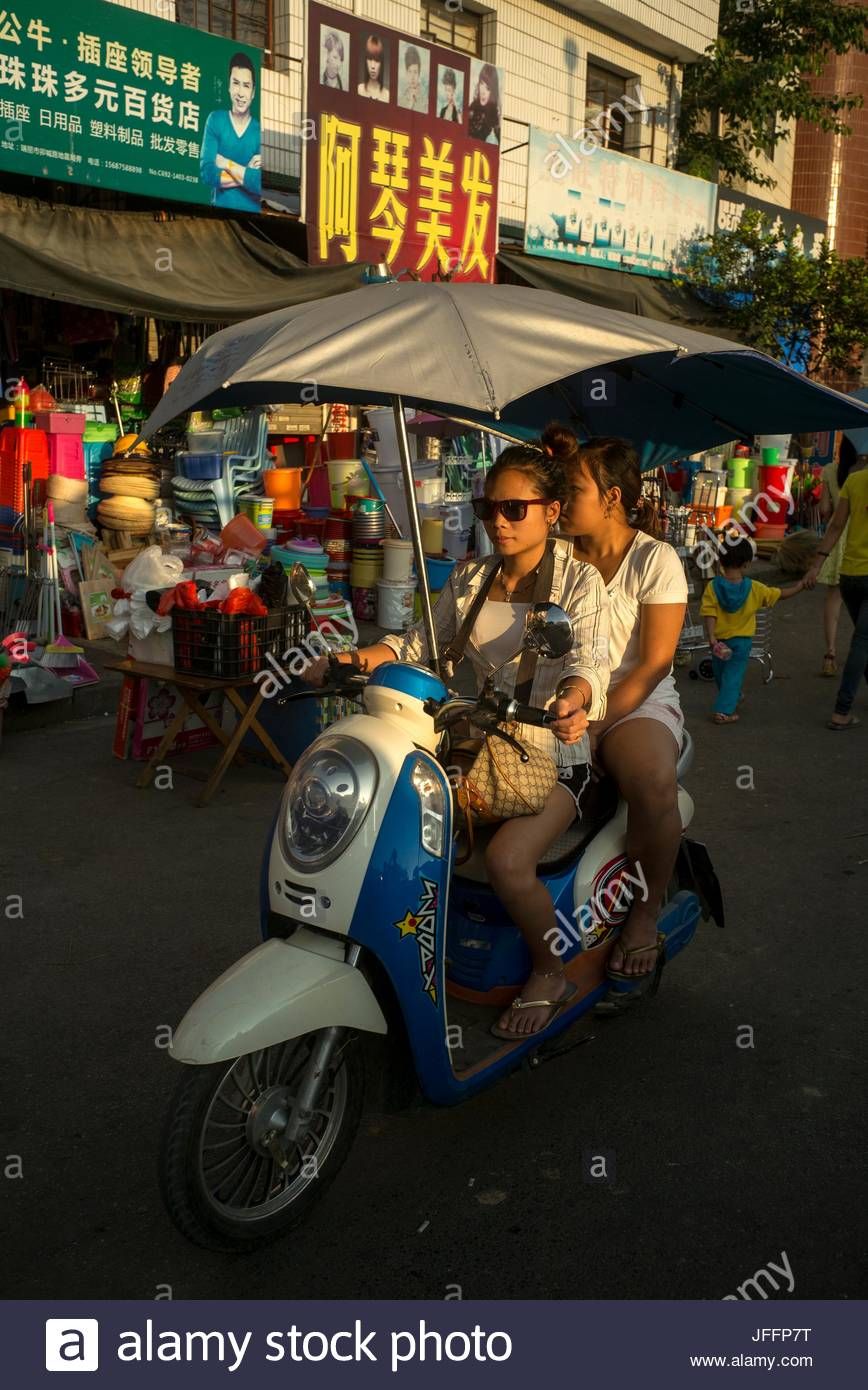 A woman drives a motor scooter with a male passenger past shops in Ruili. - Stock Image