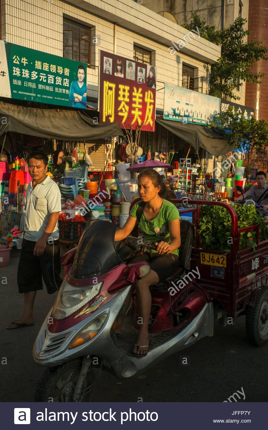 A woman pulls a trailer with produce to market with a scooter. - Stock Image
