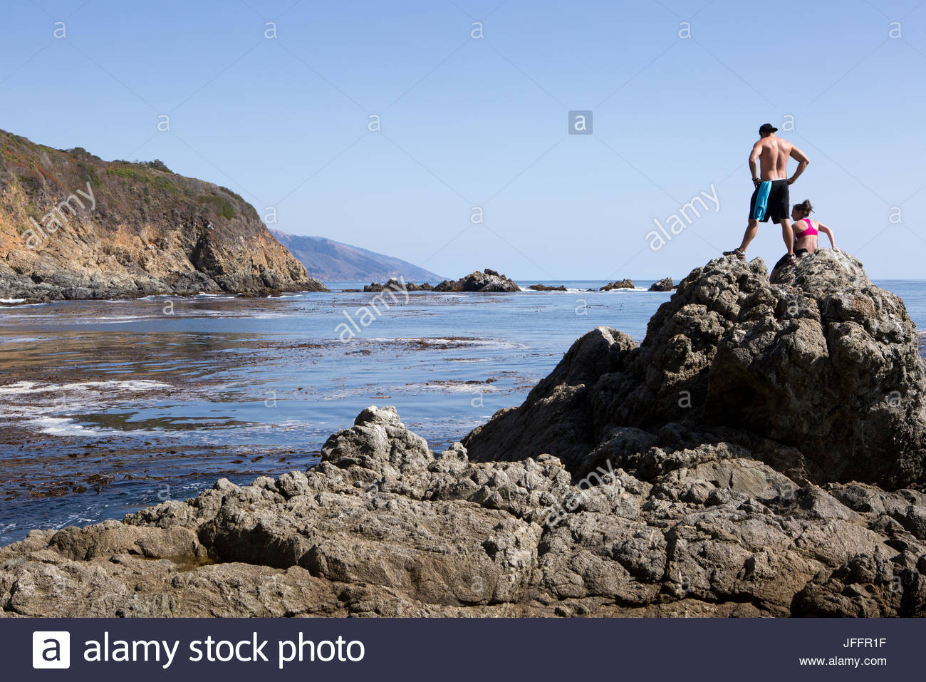 Two hikers pause on rock formations on the Big Sur coast. - Stock Image
