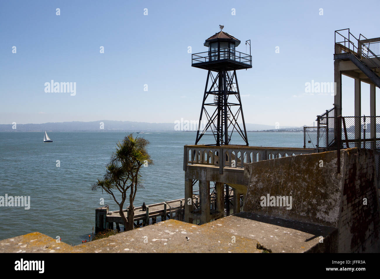 A watchtower on Alcatraz Island, and a scenic view of the water and a sailboat off shore. - Stock Image