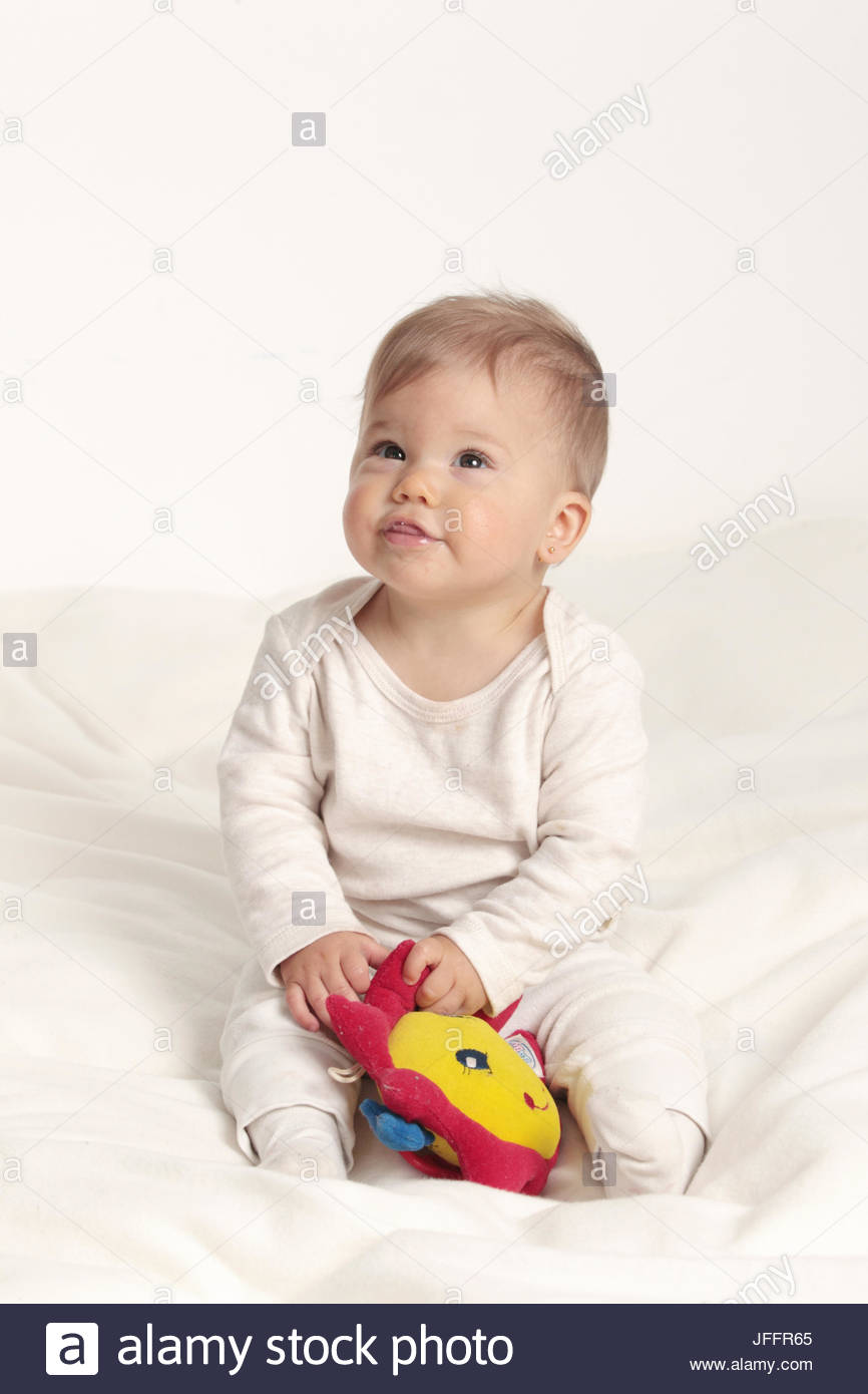 Portrait of an eight-months-old baby girl sitting with a toy. - Stock Image