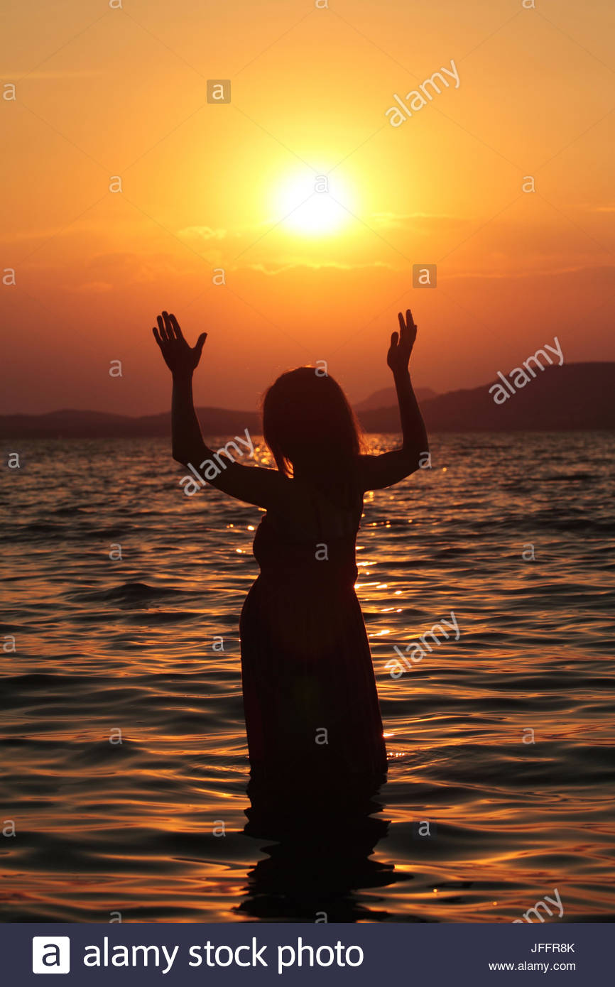 A pregnant woman, in silhouette, standing in the water at Lake Balaton at sunset. - Stock Image