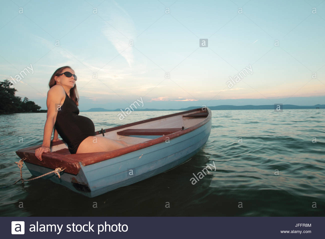 A pregnant woman relaxing in a rowboat at sunset, on Lake Balaton. - Stock Image