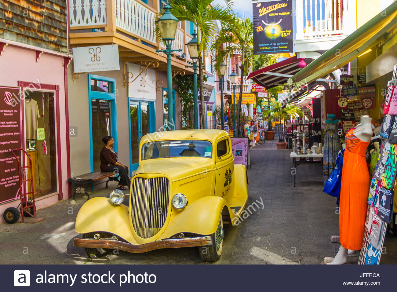 A yellow antique car in the colorful downtown marketplace in Philipsburg. - Stock Image