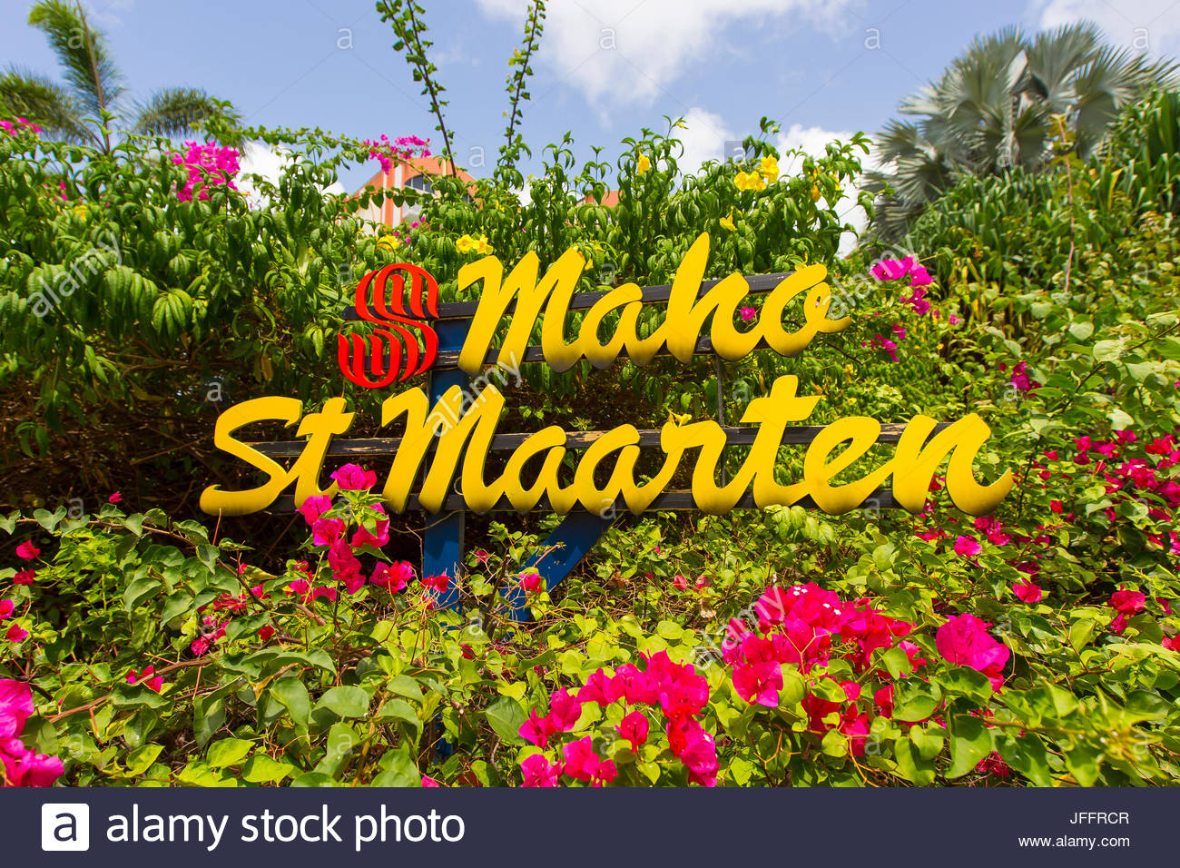 A colorful welcome sign among bright tropical flowers at Maho Beach, Saint Martin. - Stock Image