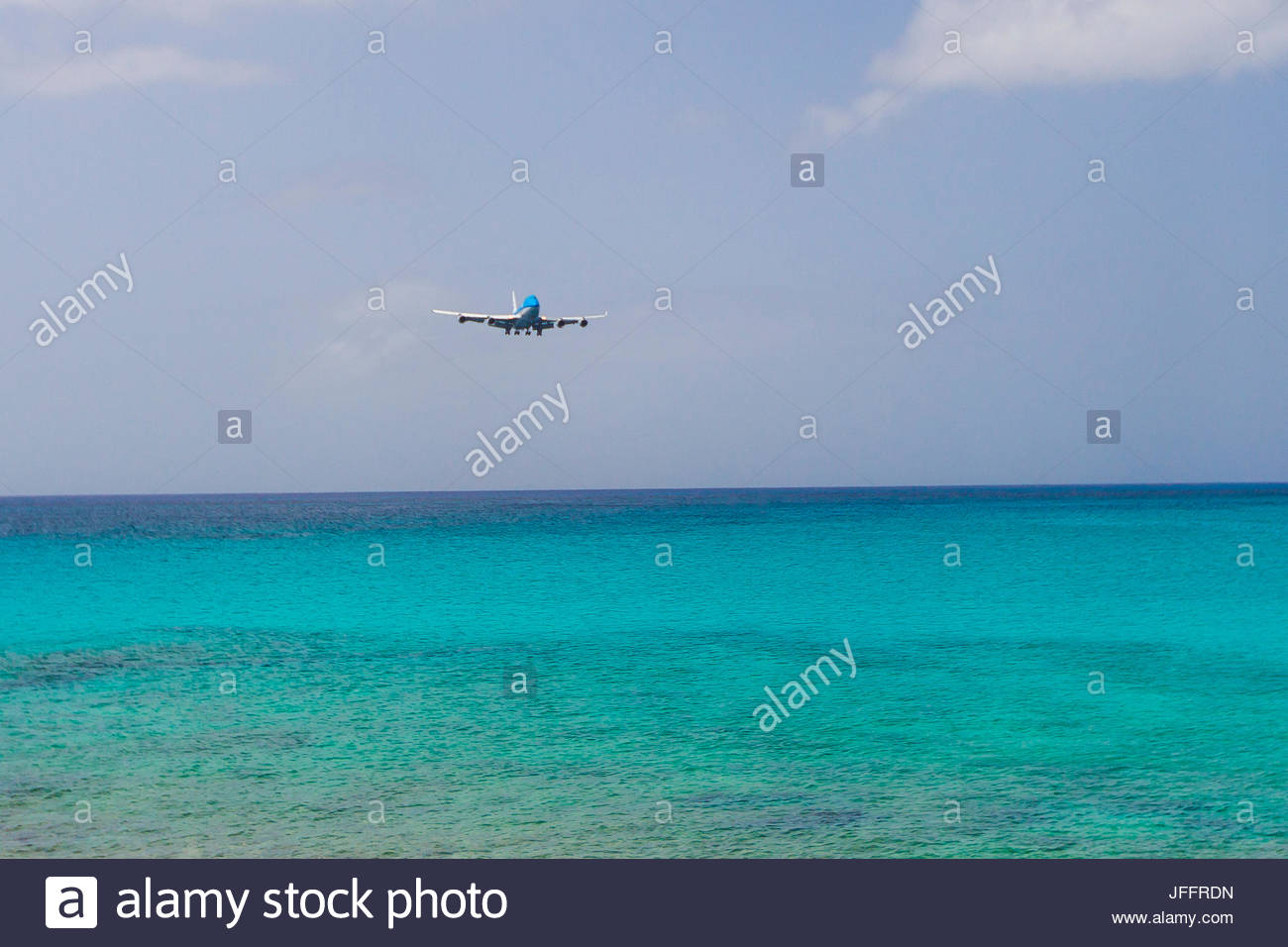 A jumbo jet airplane flying low over the Atlantic Ocean before landing at Princess Juliana Airport. - Stock Image
