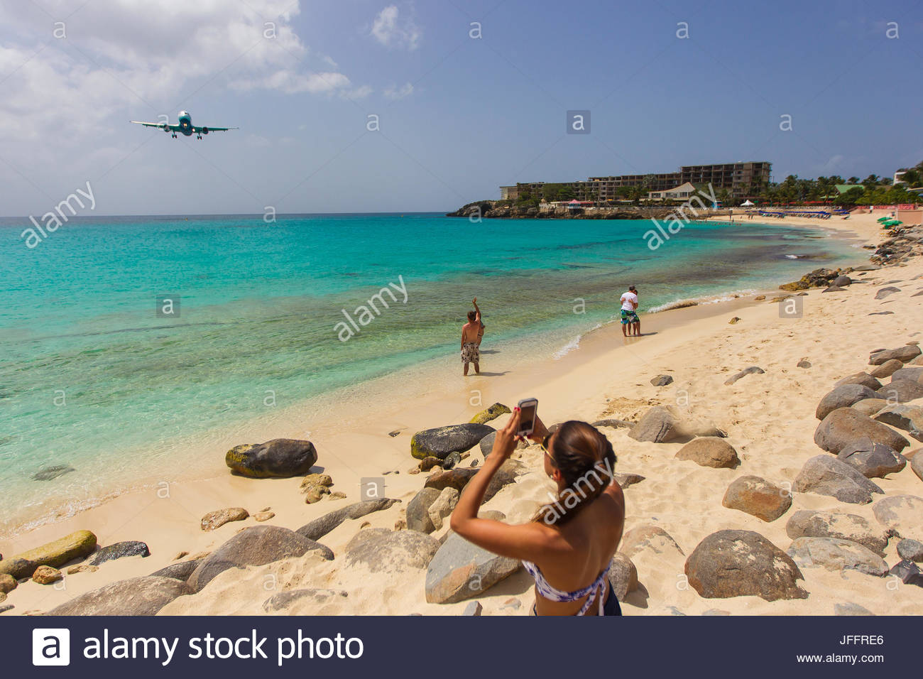 A jumbo jet airplane flying low over the water at Maho Beach before landing at Princess Juliana Airport. - Stock Image