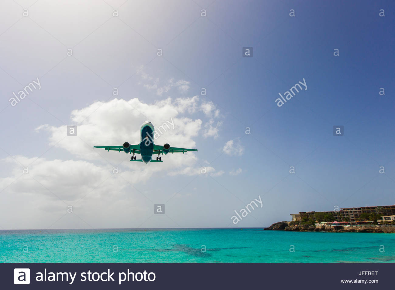 A jumbo jet airplane flying low over the Atlantic Ocean just before landing at Princess Juliana Airport. - Stock Image