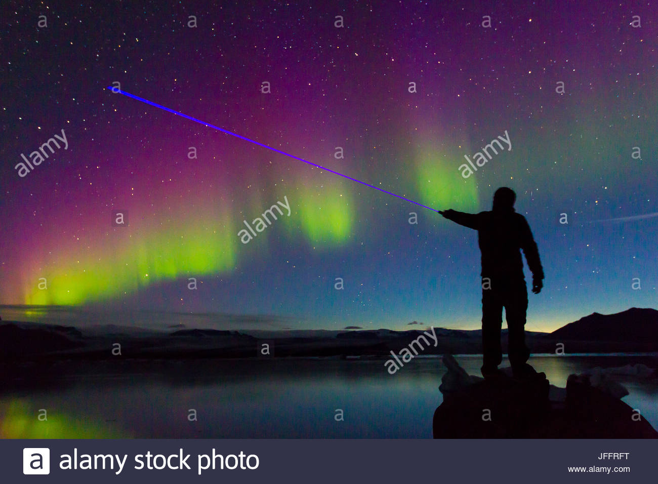 A man shining a blue laser at the Northern Lights during a geomagnetic solar storm so intense the lights reflecting - Stock Image