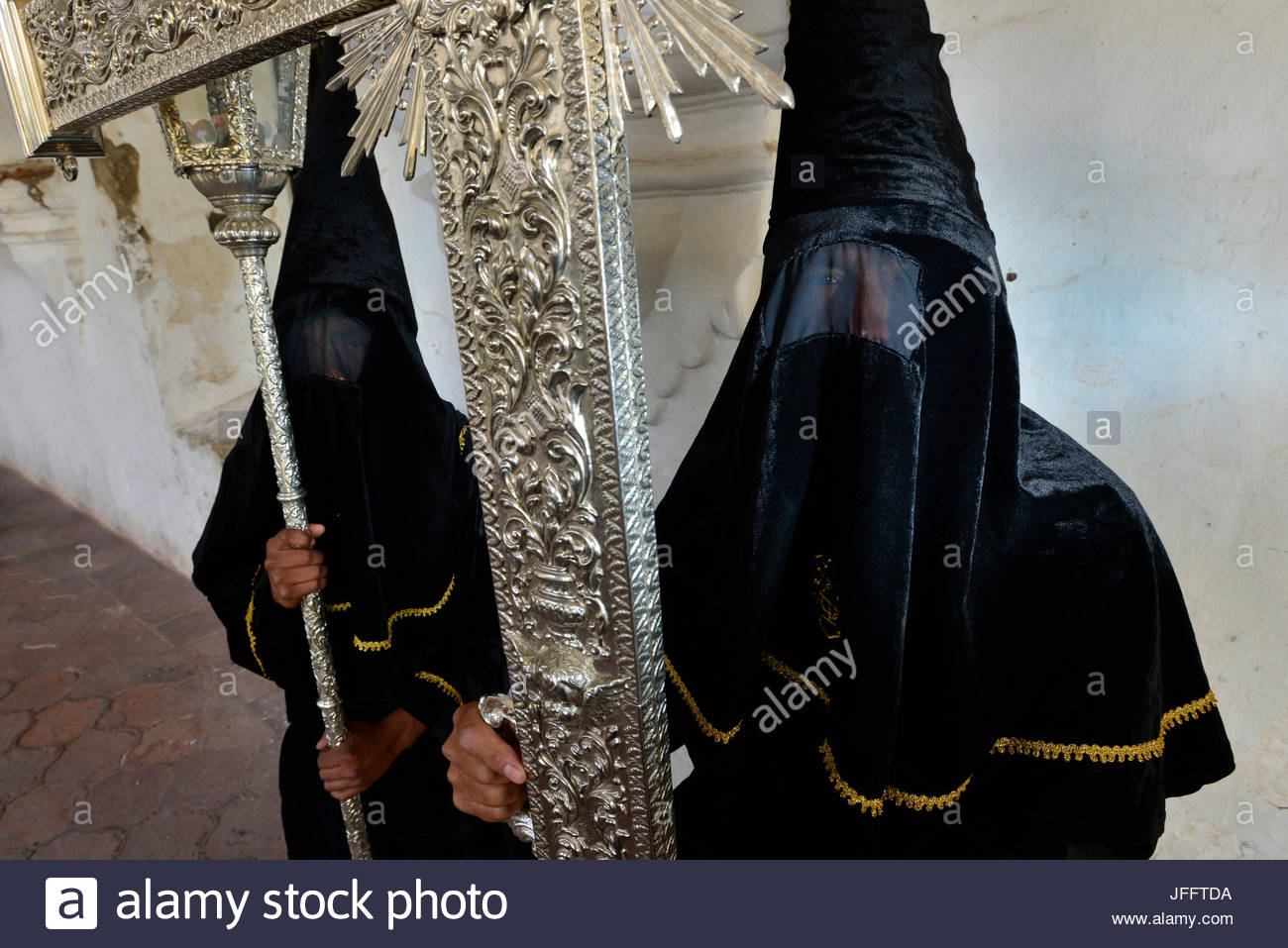 Penitents carrying a silver cross. - Stock Image