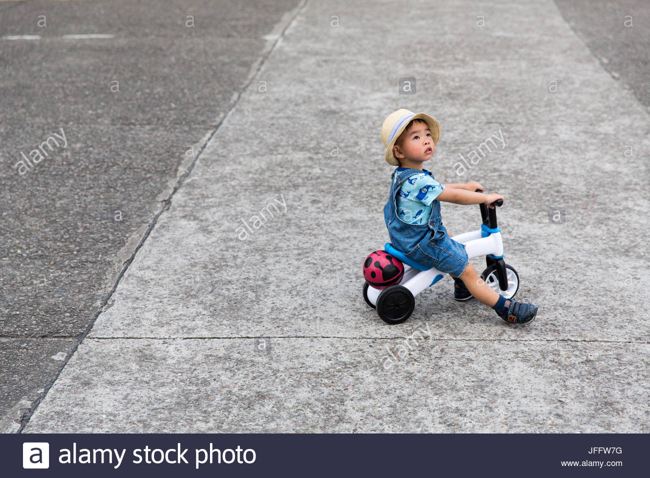 A child riding a three wheeled scooter in a park in Taipei. - Stock Image