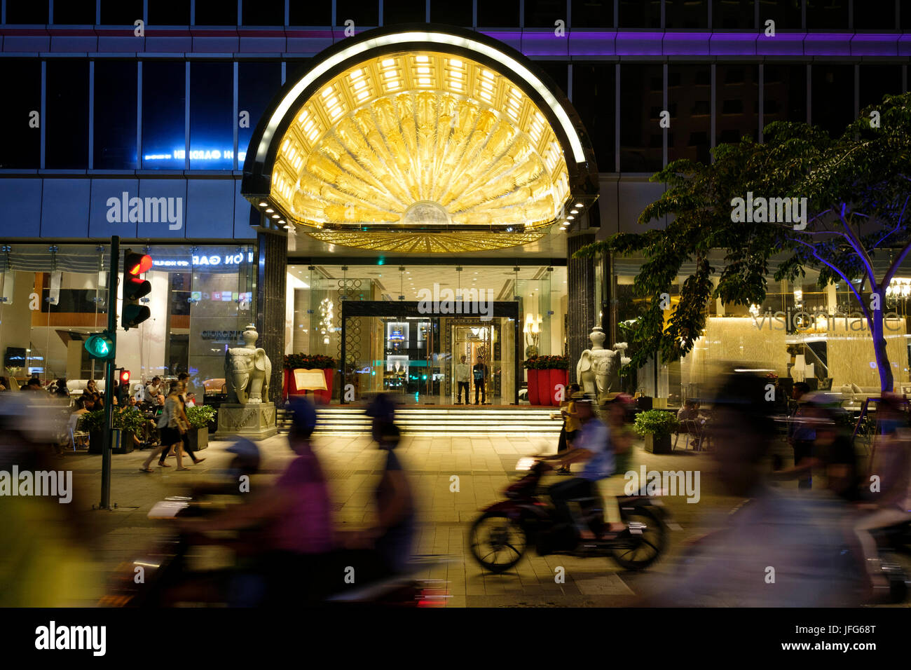 Scooters passing in front of the Reverie Saigon hotel in Ho Chi Minh City, Vietnam, Asia - Stock Image