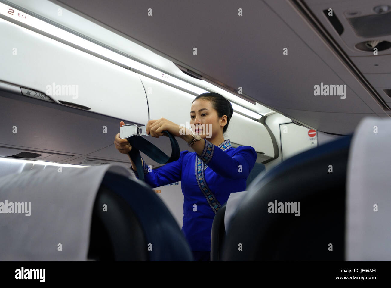 Flight hostess in uniform showing how to use the airplane seat belt during safety procedures - Stock Image