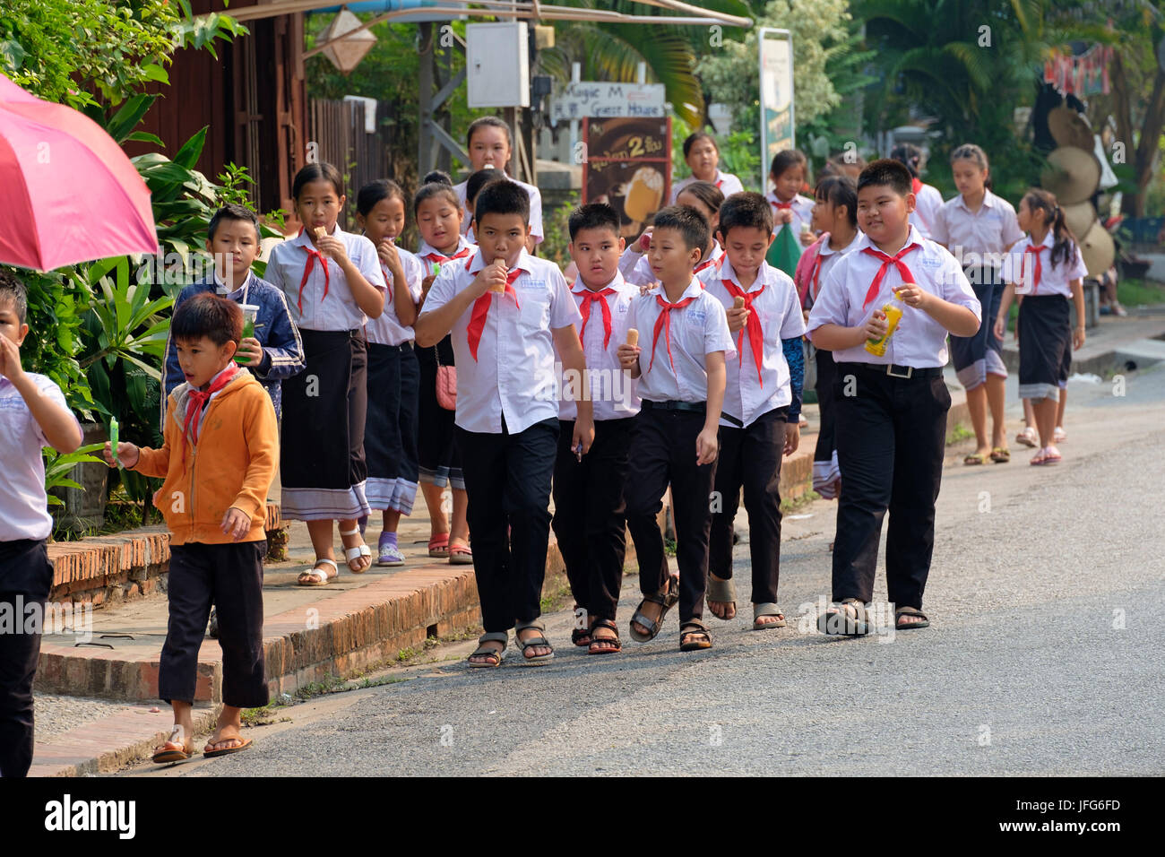 Overweight children eating junk food during a school trip in Asia - Stock Image