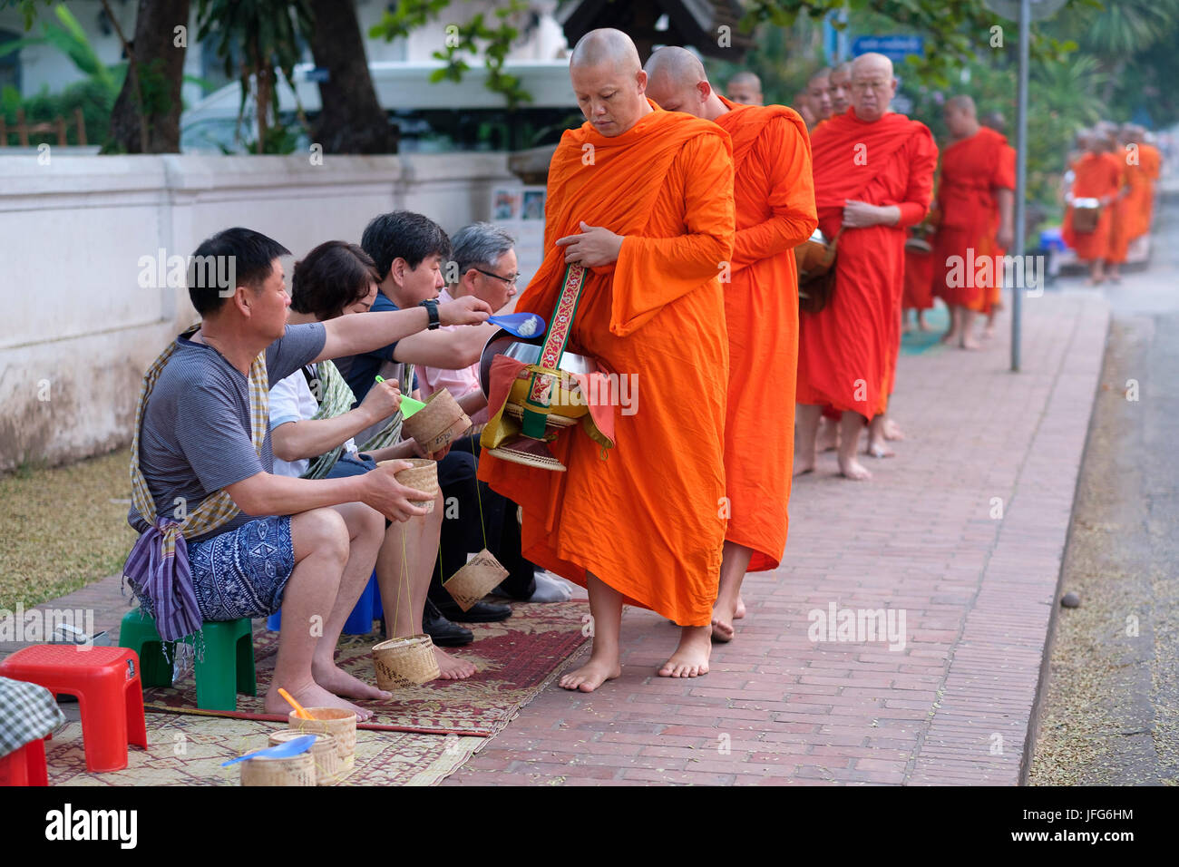 Procession of buddhist monks wearing orange robes at dawn to collect gifts on the streets of Luang Prabang, Laos, - Stock Image
