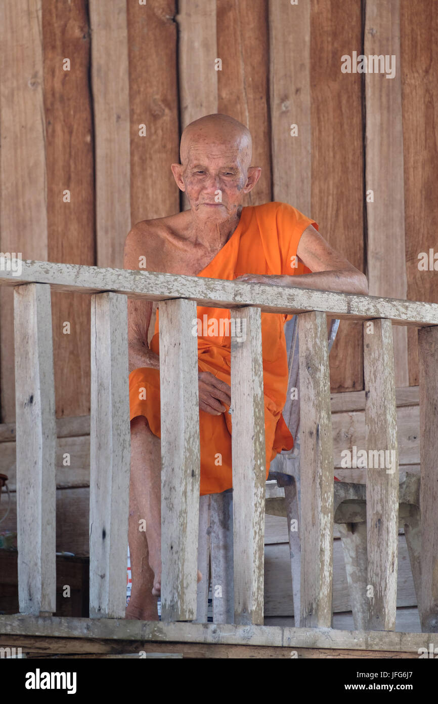 Old buddhist monk wearing orange clad robe - Stock Image