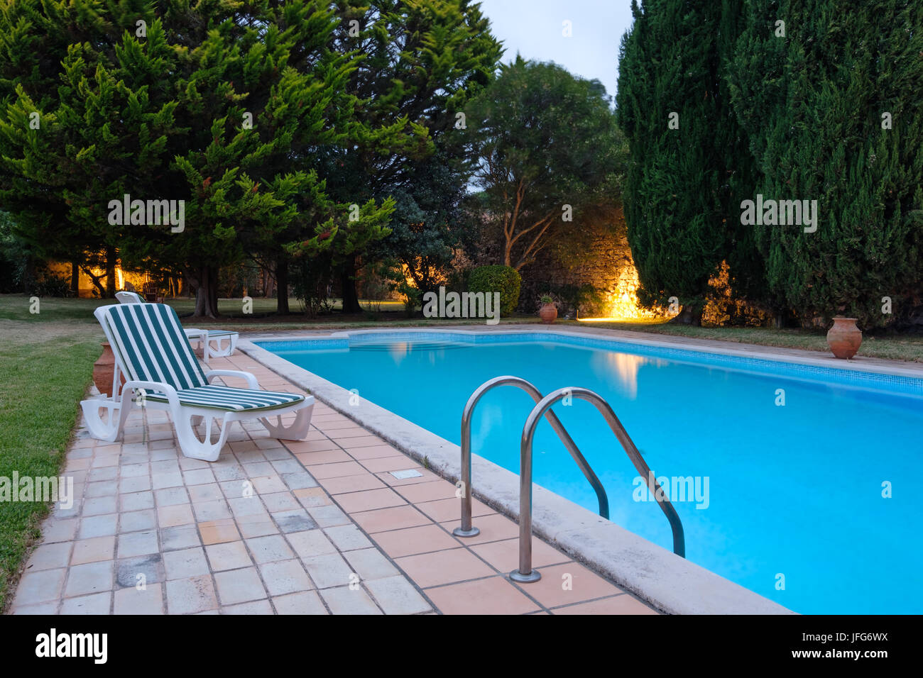 Deck chair next to outdoor swimming pool - Stock Image