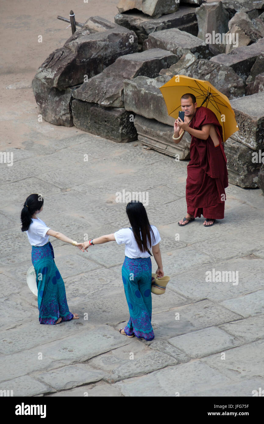 Buddhist monk taking pictures of two girls on holidays using his smartphone while visiting Angkor Wat temple complex Stock Photo