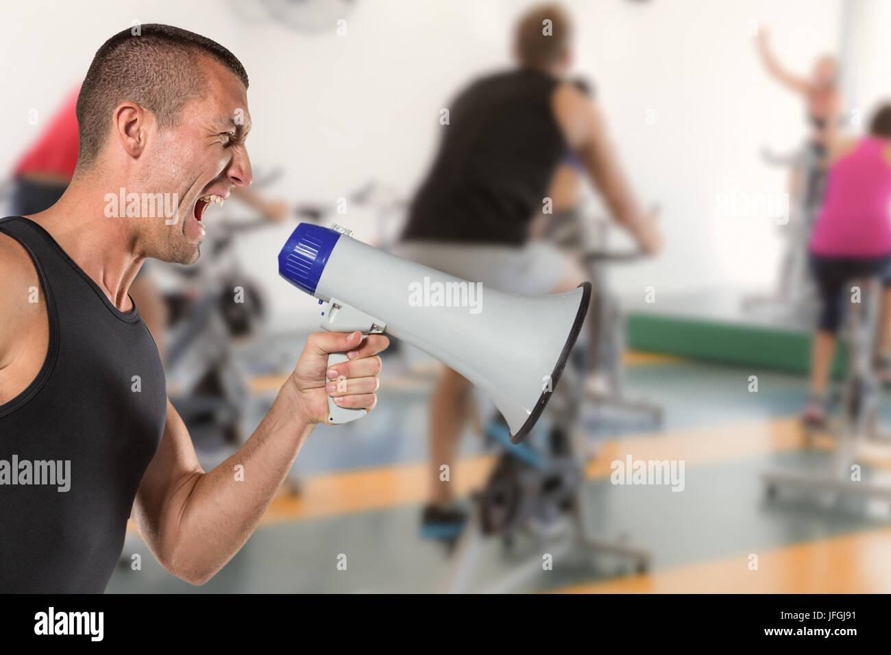 Composite image of irritated male trainer yelling through megaphone Stock Photo
