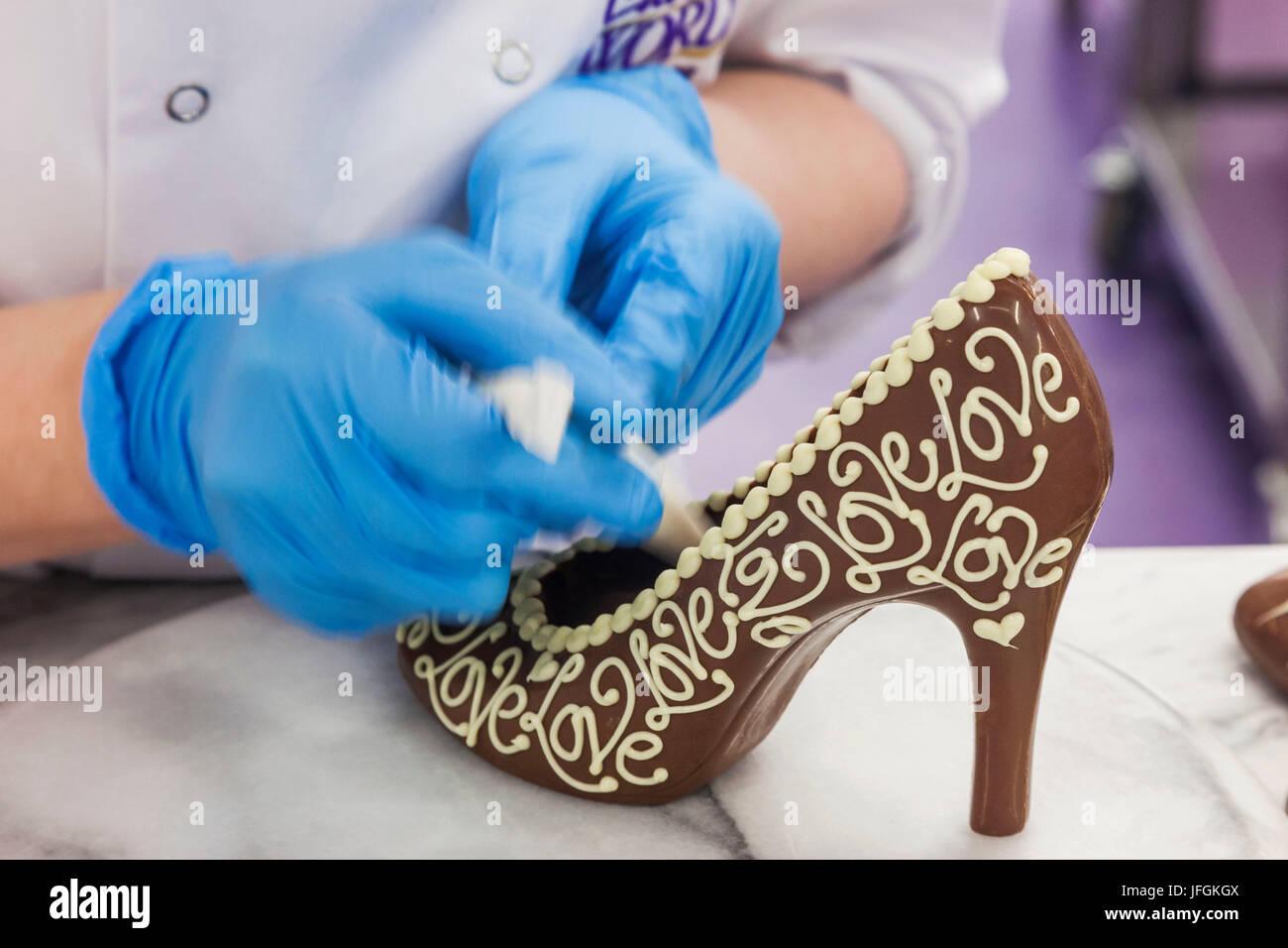 England, Birmingham, Bournville, Cadbury World, Woman Decorating Chocolate Shoe - Stock Image