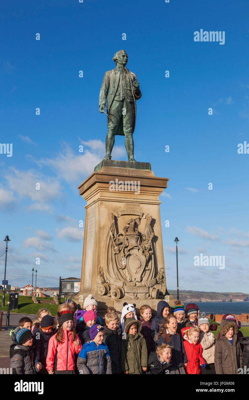 England, Yorkshire, Whitby, Captain Cook Statue and School Children - Stock Image