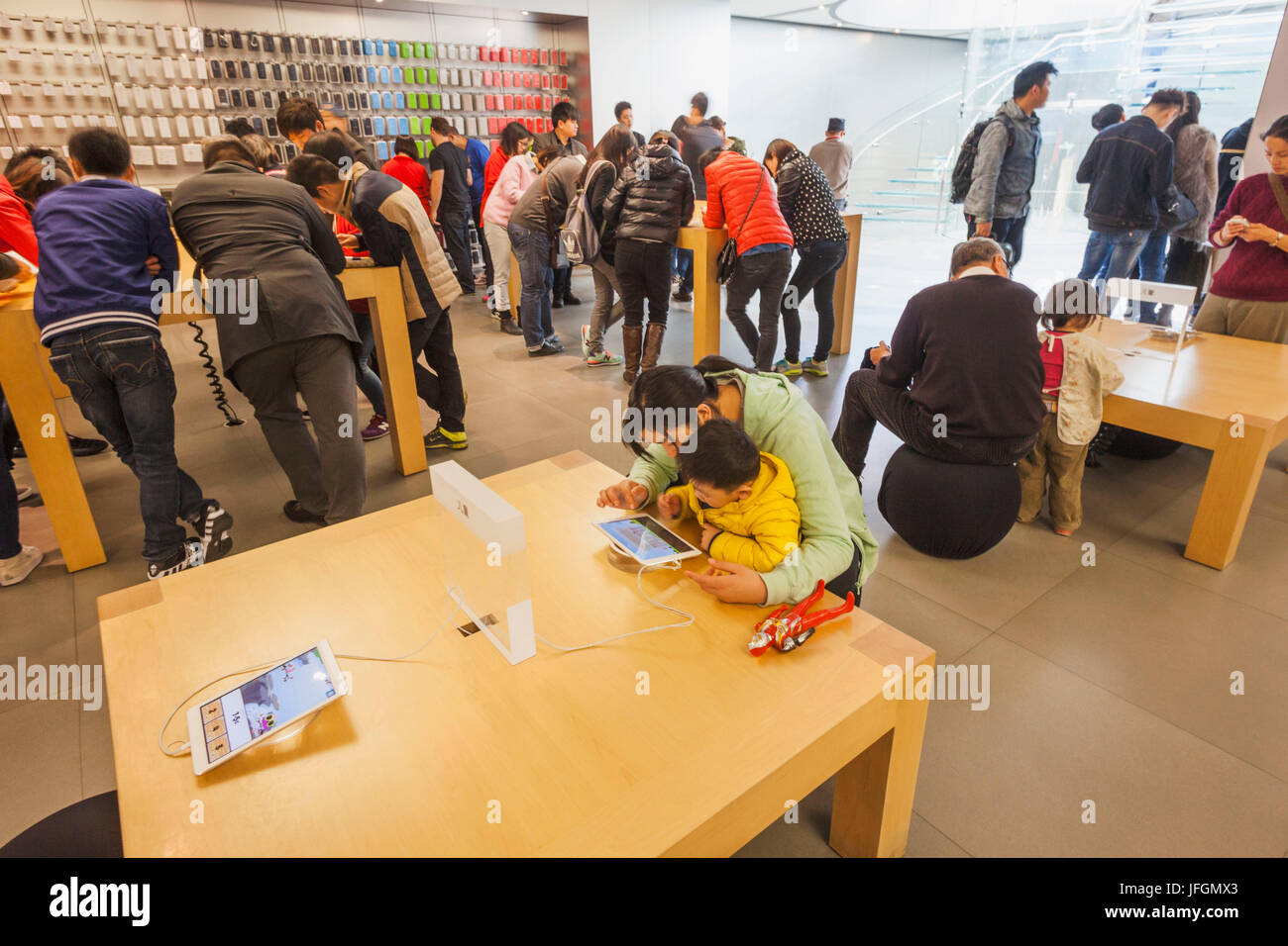 China, Shanghai, Nanjing Road, Interior of Apple Store, Mother and Child Playing with Computer Stock Photo