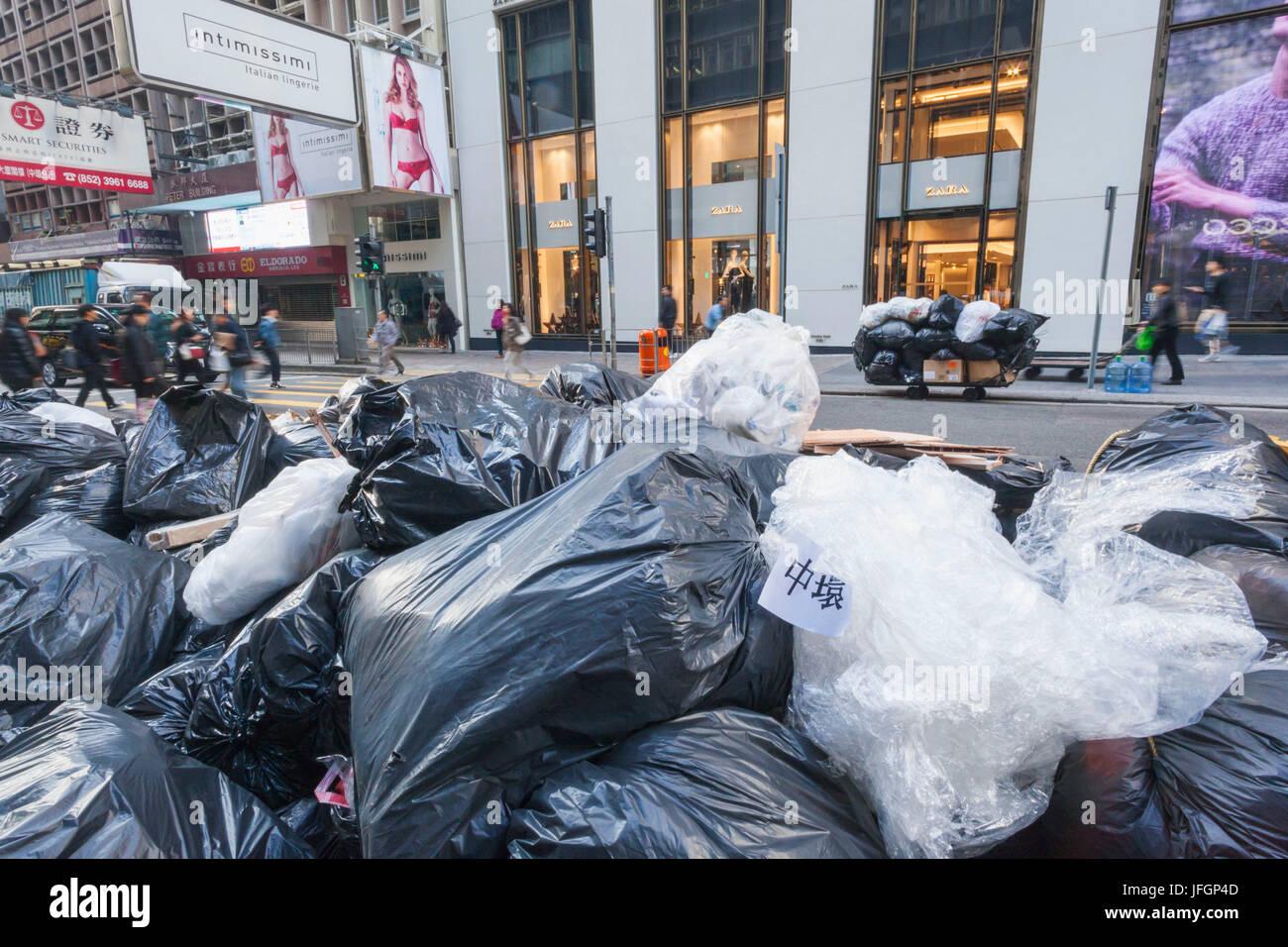 China, Hong Kong, Refuse Sacks Waiting Collection - Stock Image