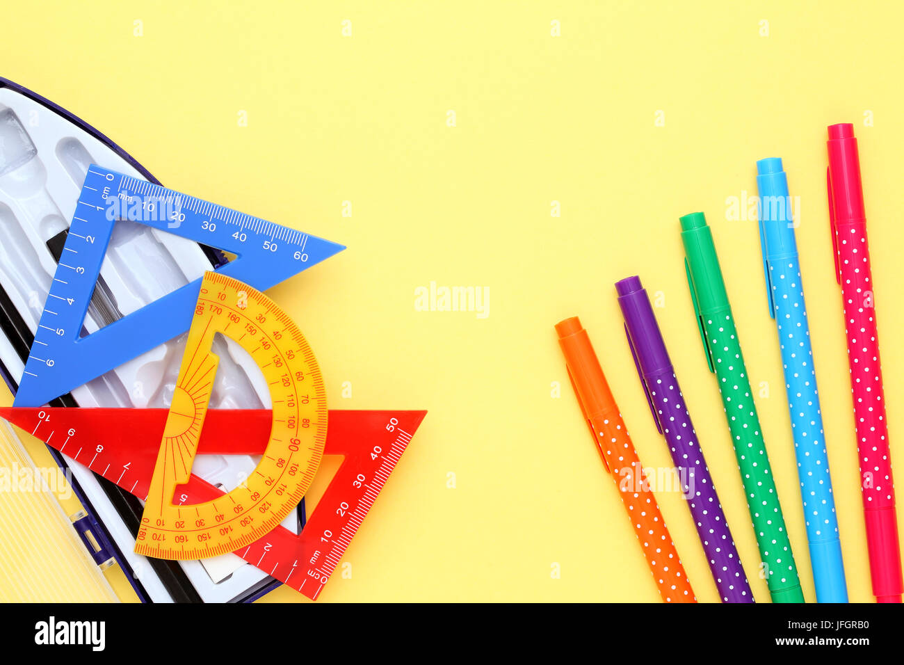 Multicolored rulers and pen on yellow background - Stock Image