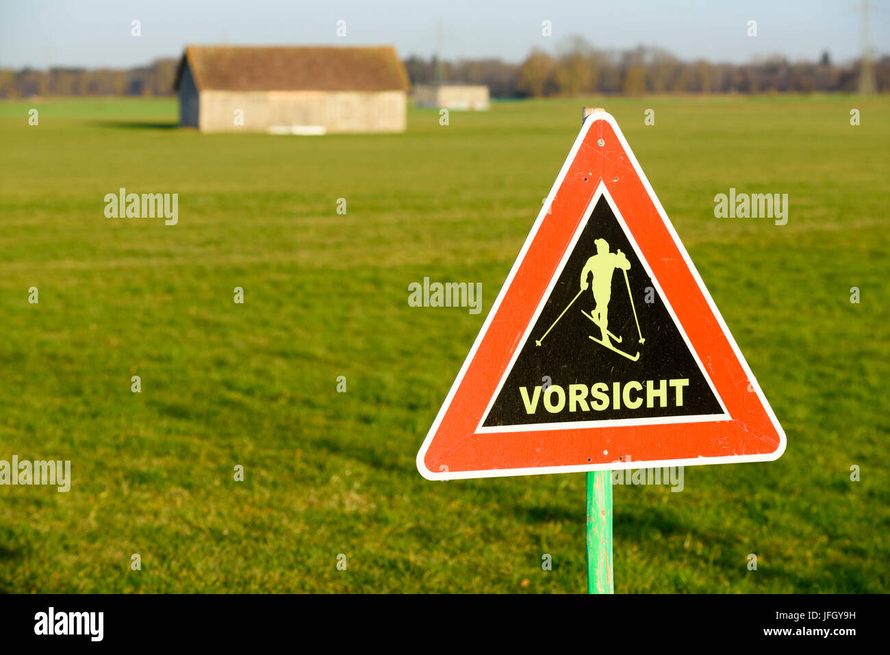 Road sign in street warns about cruising skiers on cross-country trail, green meadows, springlike temperatures about Stock Photo