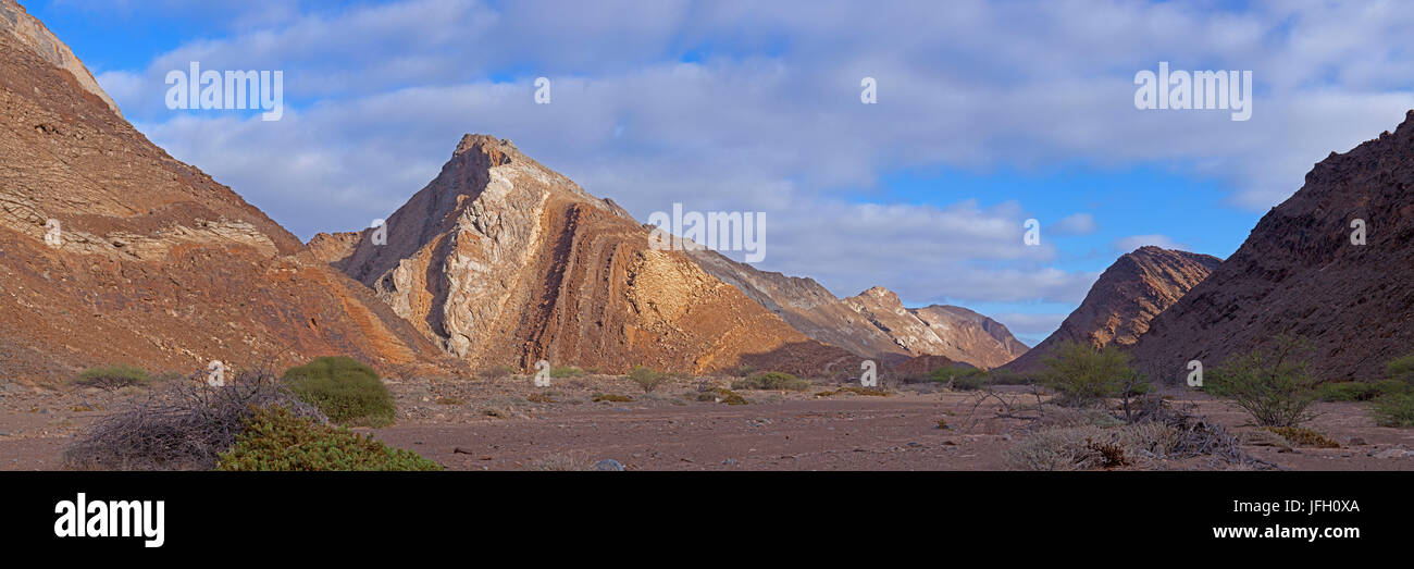 Cliff faces with layer-shaped erosion and rejections, Damaraland, Namibia, panorama - Stock Image