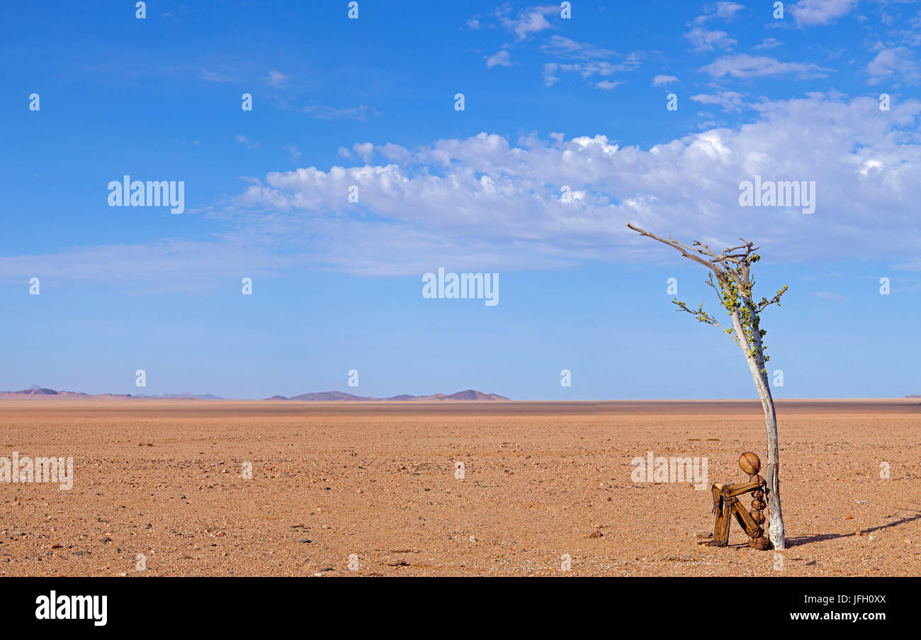 Sculpture from wire and ballstones, seated character under small tree, desert, thirst - Stock Image