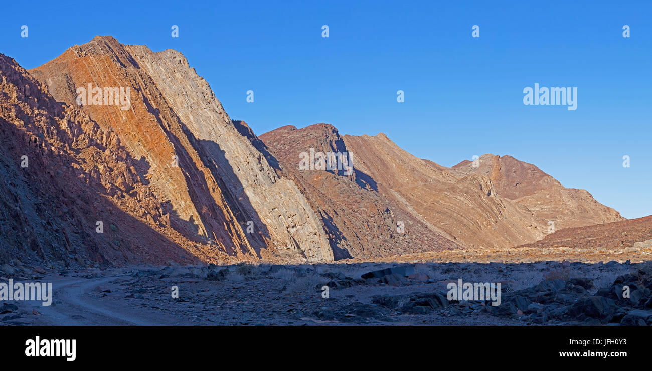 opened up cliff faces with inclined rejections, Damaraland, Namibia, panorama - Stock Image