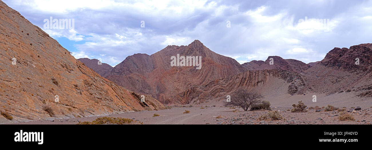 eroded cliff faces with wave-shaped rejections and sand drift, Damaraland, Namibia, panorama - Stock Image