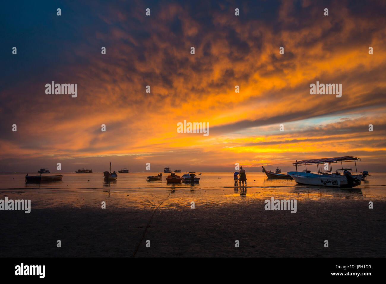 Family with small child on the beach in the water, boats in the sea at sundown, island Koh Tao, golf of Thailand, - Stock Image