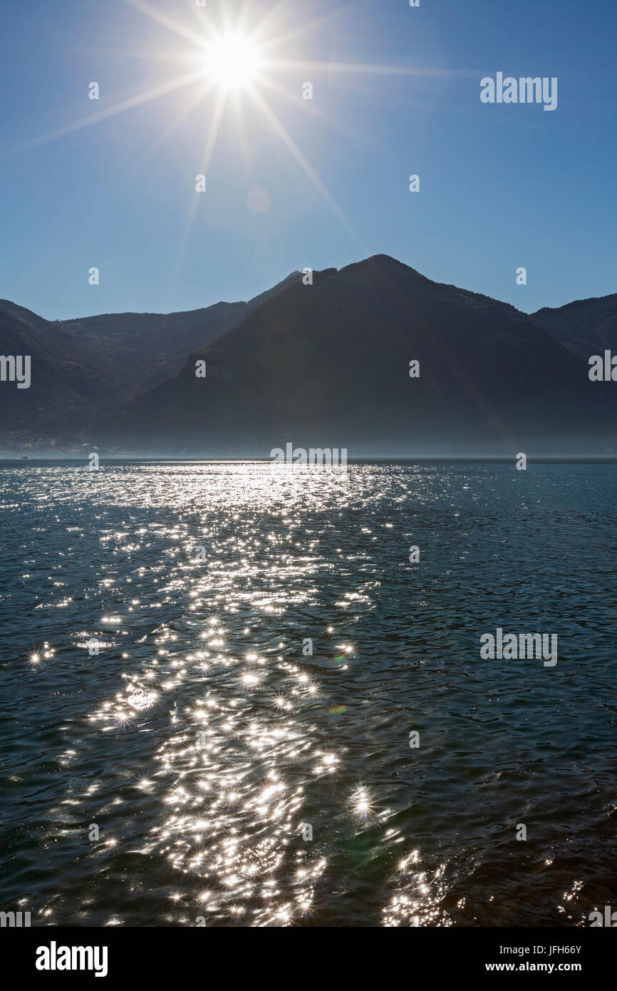 Scenic view of lake and silhouette of mountains - Stock Image