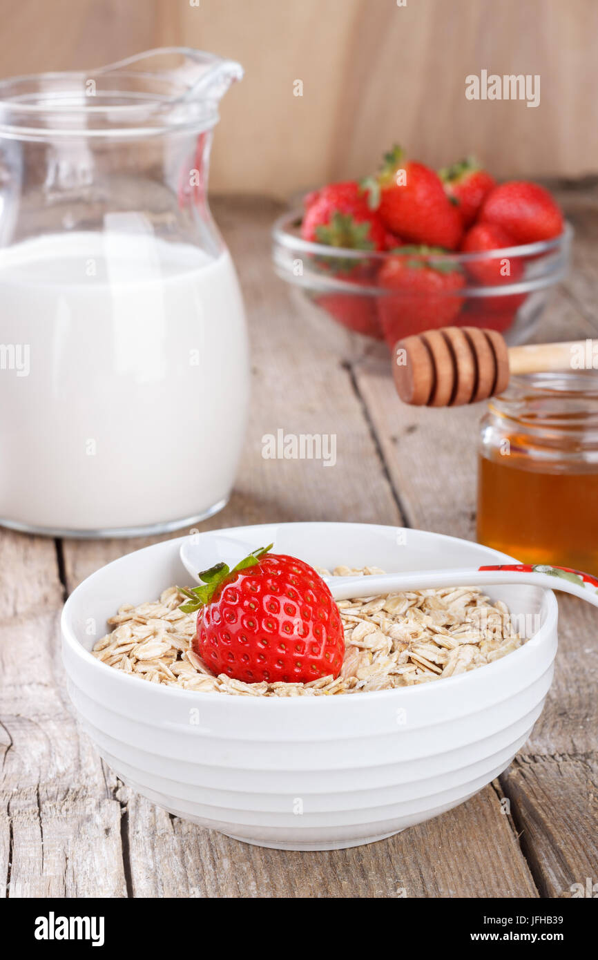 Healthy cereal with milk, honey and strawberry - Stock Image