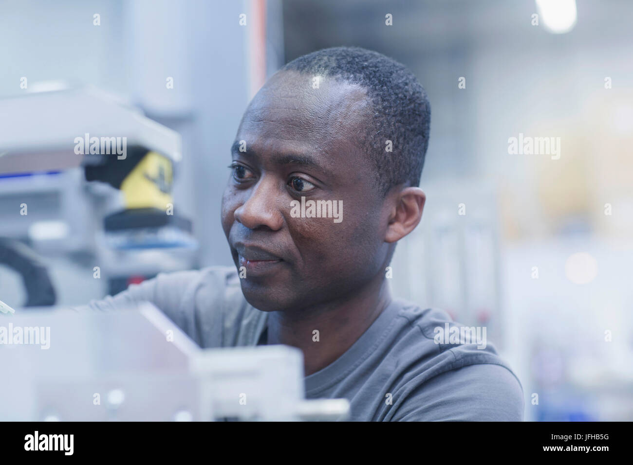 Close-up of worker repairing machine at engineering plant - Stock Image