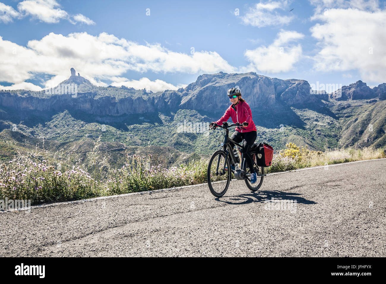Woman riding electric bicycle on mountain road - Stock Image