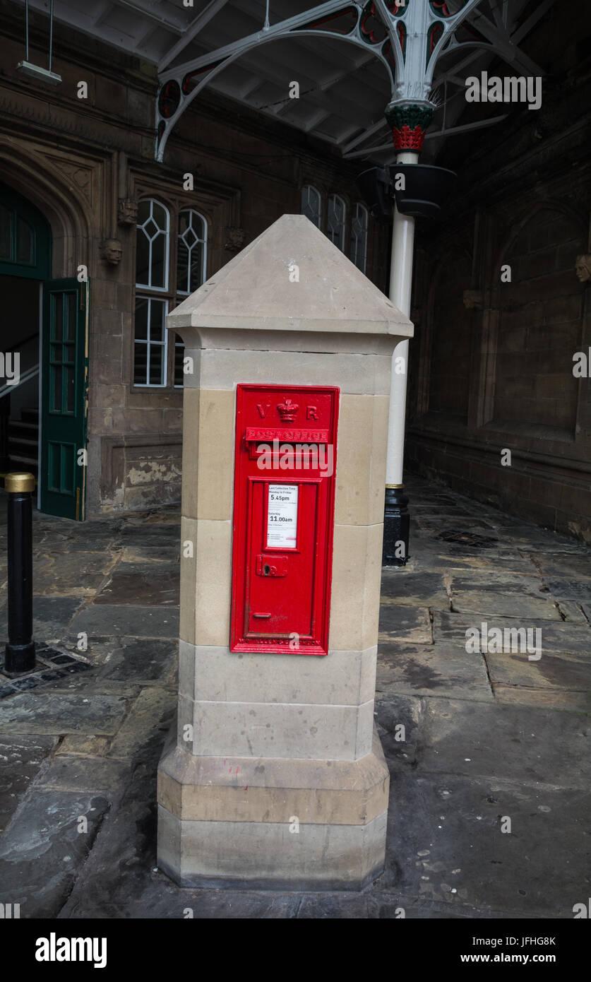 Red rectangular Victorian postbox built into a stone pillar at Shrewsbury train station.  Shropshire, UK - Stock Image