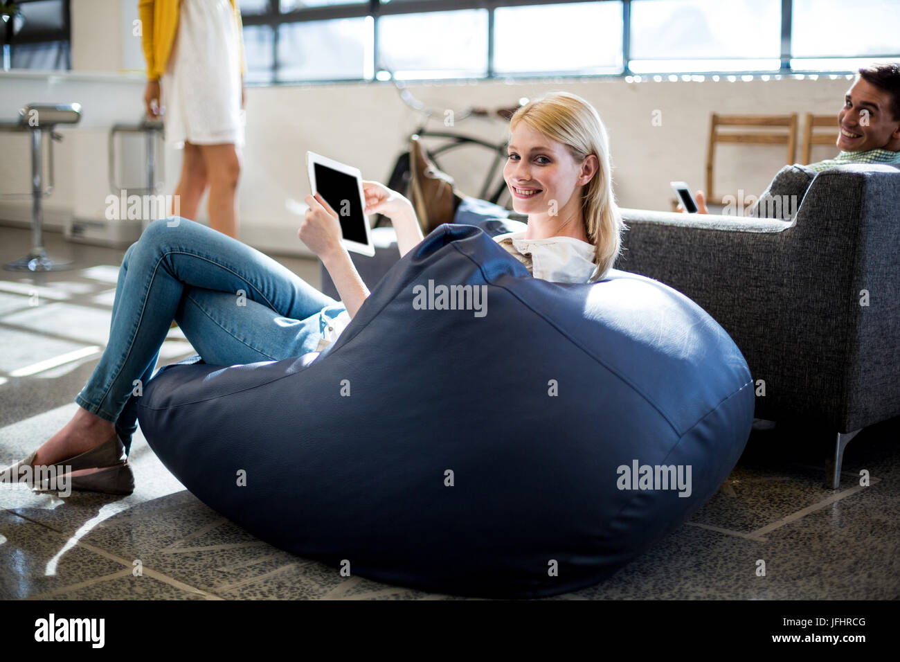 Young woman sitting on a bean bag holding digital tablet - Stock Image