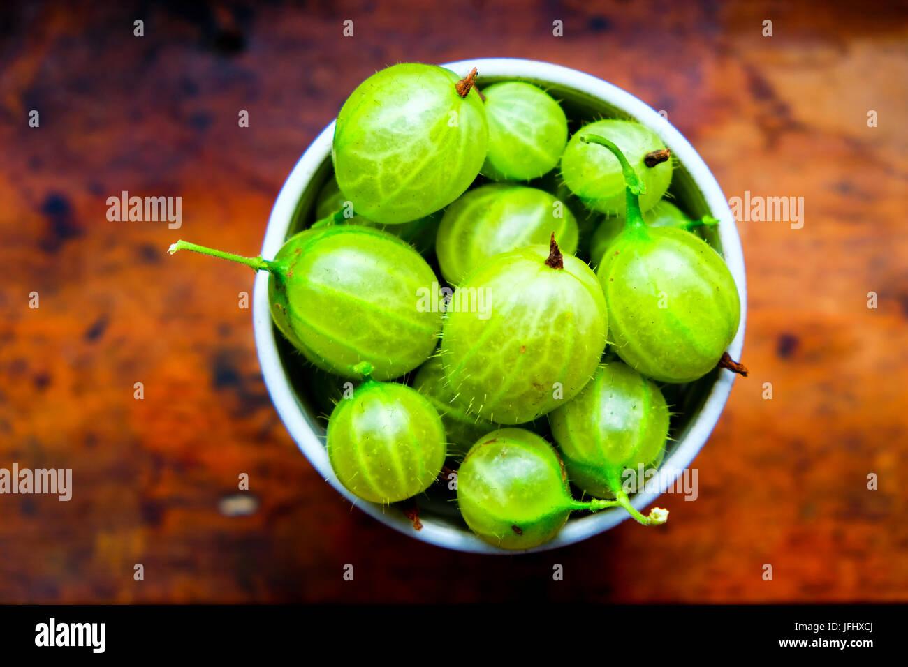 small bowl of Gooseberries in grey pottery bowl, the bowl is full of gooseberries, there are 5 green gooseberries Stock Photo