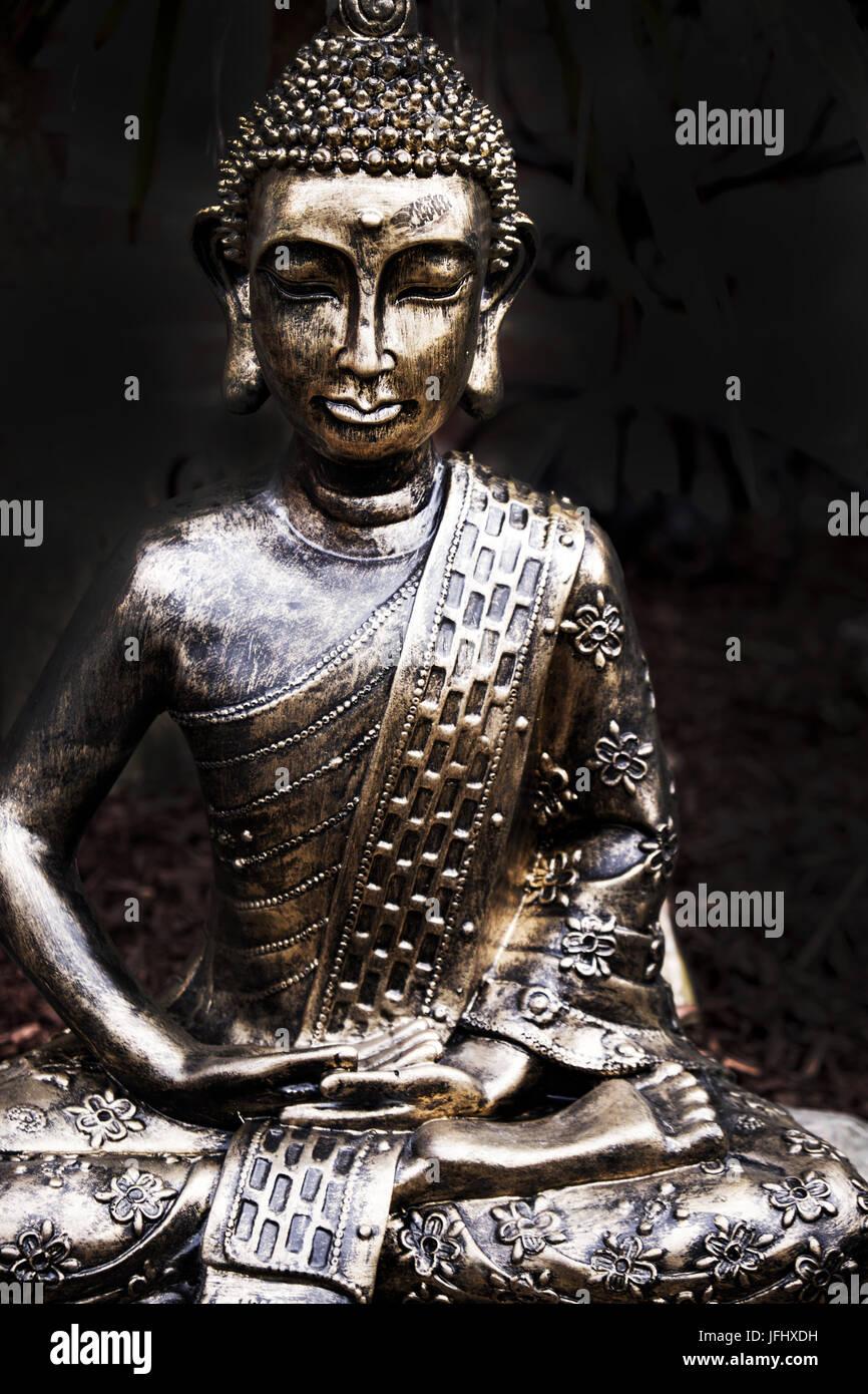 buddha statue sitting cross legged in a garden, gold/silver datk background - Stock Image