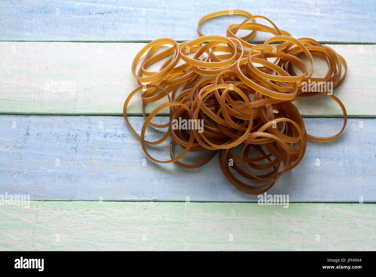 Rubber Bands on Wooden Background - Stock Image