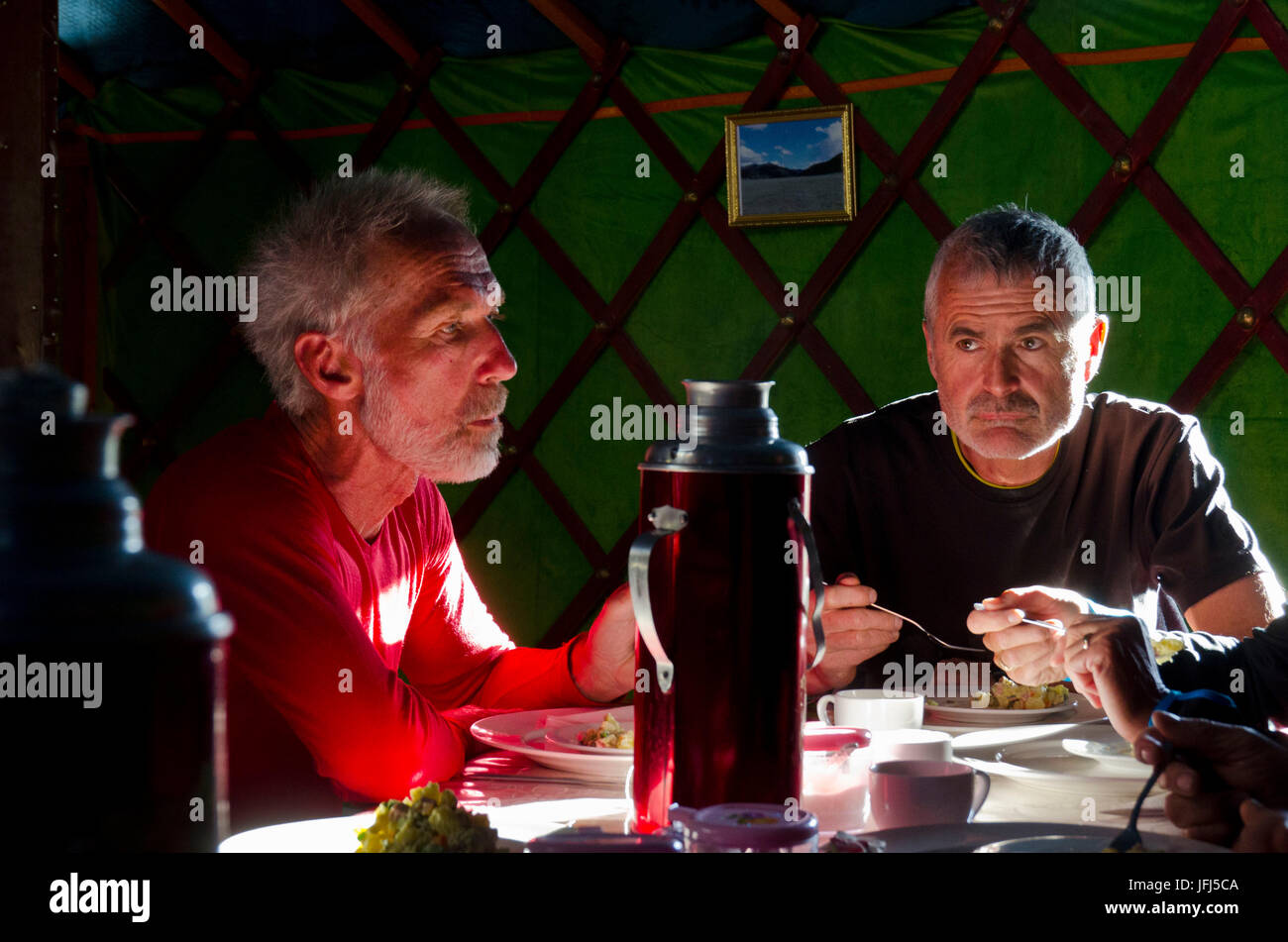 Mongolia, Central Asia, yurt camp at Tsenkher, two men having dinner in a yurt - Stock Image