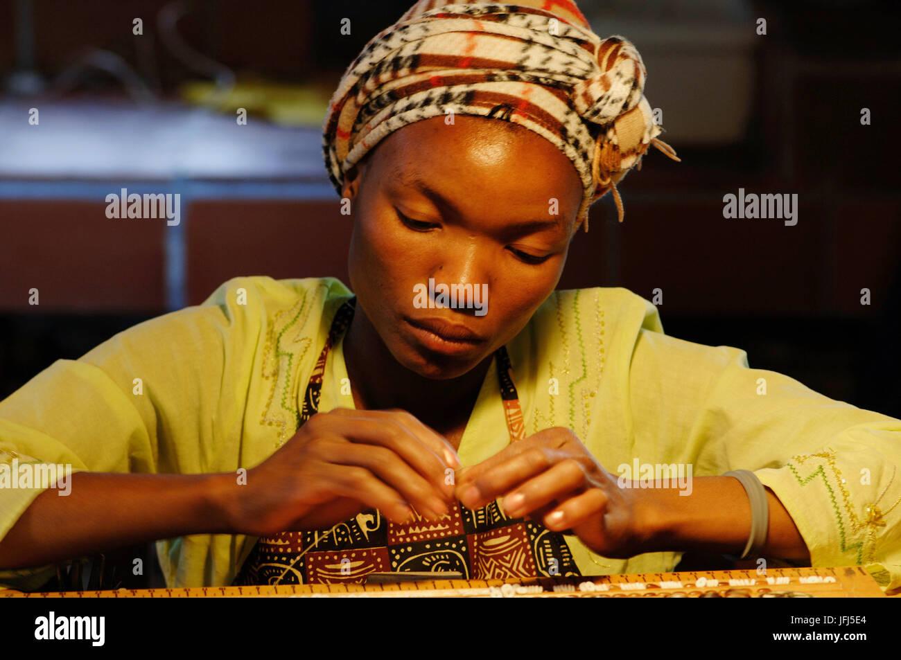 Africa, Namibia, Kiripotib farm of Claudia von Hase, goldsmiths atelier, Damara girl Dora while threading a chain - Stock Image